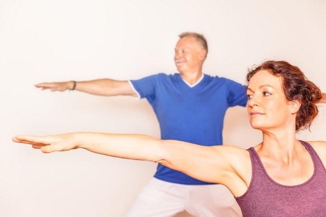 Deux personnes pratiquant le yoga (posture Virabhadrasana)